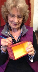 Mary painting a box